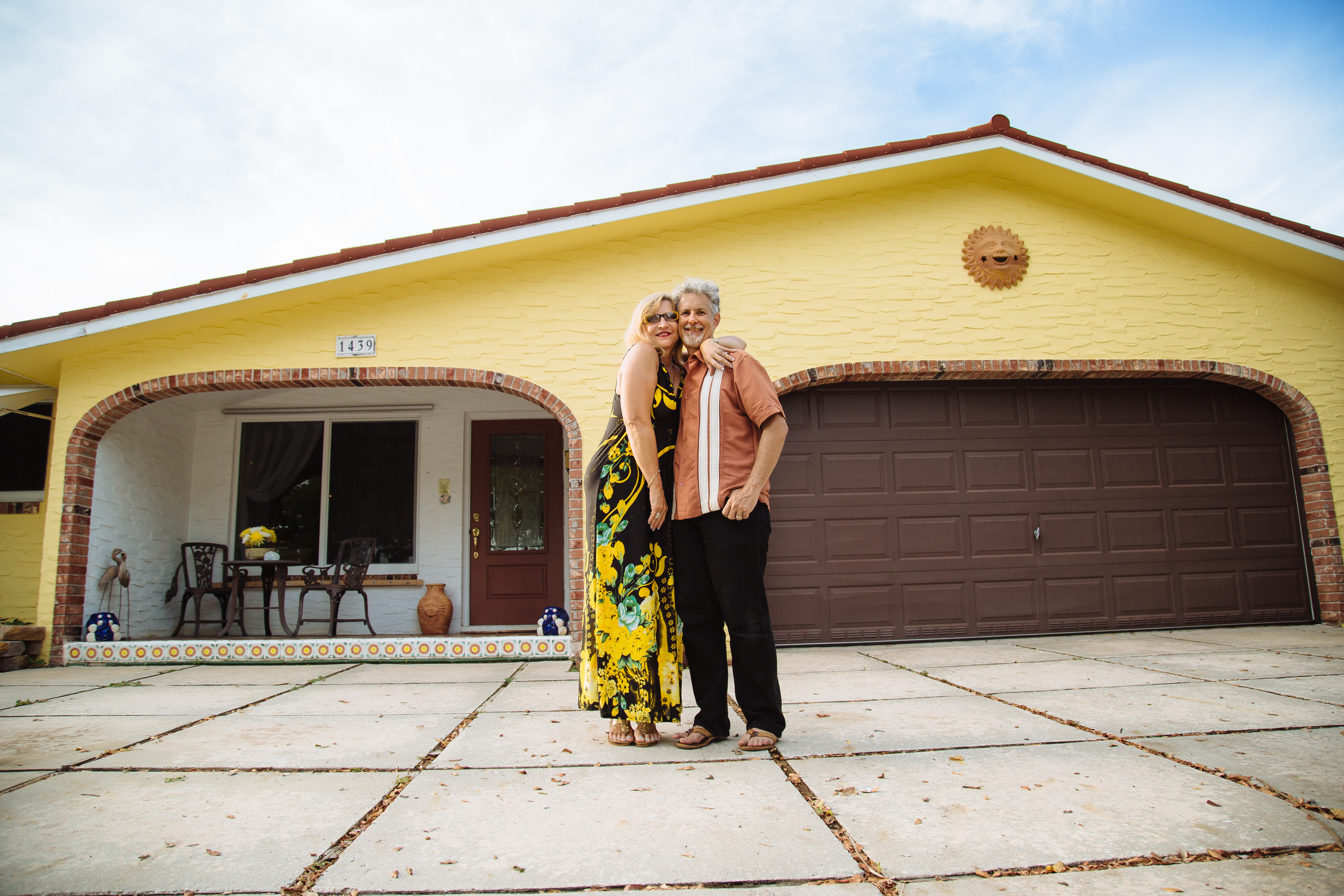 Happy couple in front of Florida home with new energy-efficient upgrades