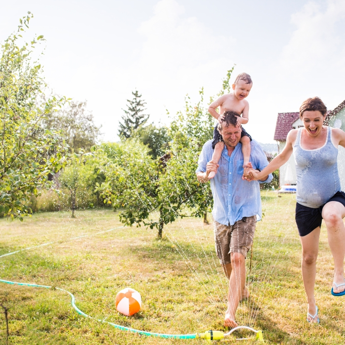 Family running through sprinklers