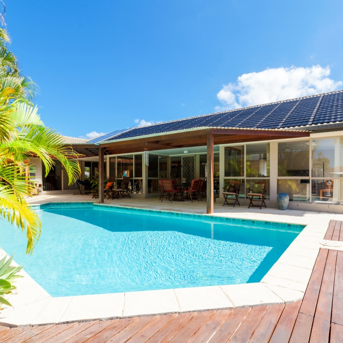 Backyard of home with solar panels and swimming pool